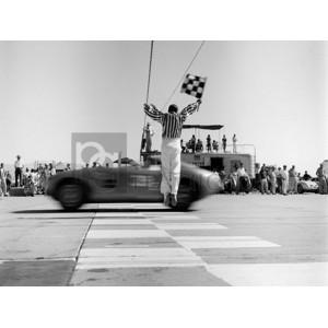 H. Armstrong Roberts - Man jumping waving checkered flag